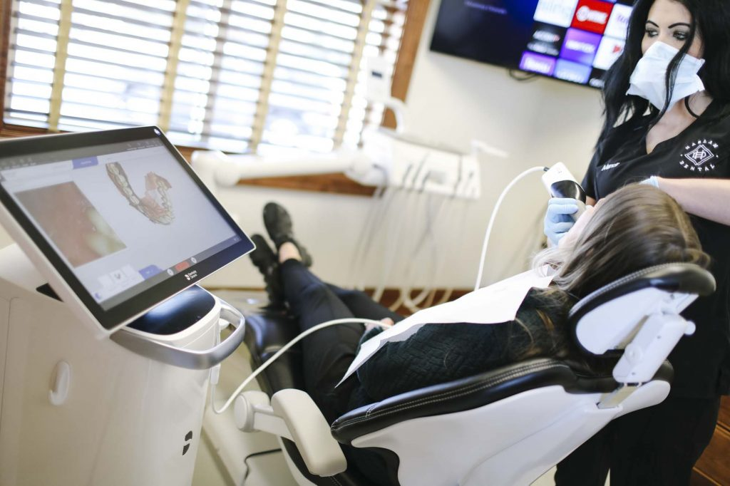 a female dental assistant uses an intraoral camera to see a 3-d model of the patients teeth